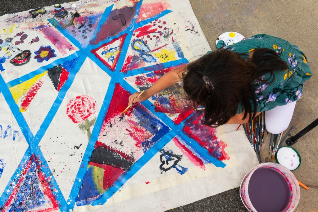 Girl painting abstract shapes on a fabric mural by Conway artist Jessica Jones at the 2019 ArtsFest.